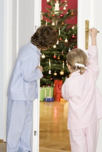 Girl and boy (3-7) standing by door watching Christmas tree, rear view