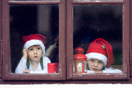 Two cute boys, looking through a window, waiting for Santa