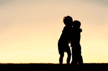 Silhouette of Two Young Children Hugging at Sunset