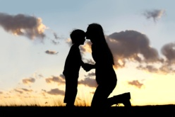 Silhouette of Mother Lovingly Kissing Little Child at Sunset