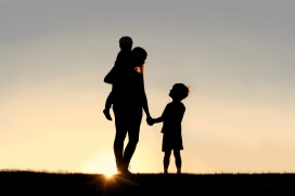 Silhouette of Mother and Young Children Holding Hands at Sunset
