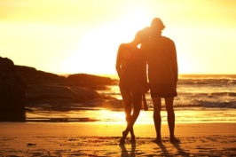 Loving couple standing by the beach looking at sunset
