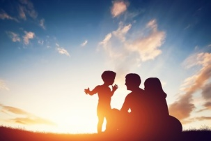Happy family together, parents with their little child at sunset.