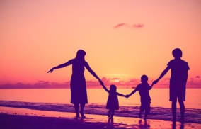 happy family with two kids walking at sunset