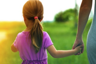 Little girl holding a hand of her mother. Family relations concept.