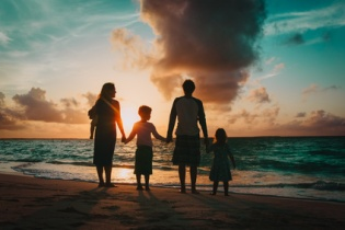 happy family with kids walk at sunset beach